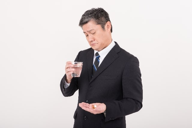 胃薬を飲む男性