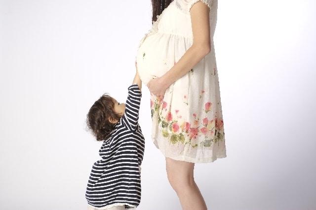 妊娠中のお腹を触る子供